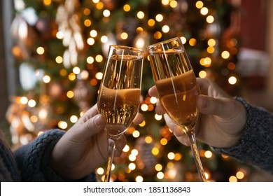 Crop close up of man and woman hold glasses with champagne clink greet congratulate with New Year. Couple celebrate Christmas winter holidays at home together, wish luck and joy. Celebration concept.