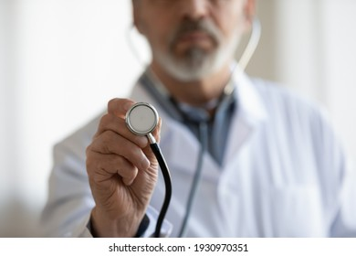 Crop close up of mature male doctor in white medical uniform hold stethoscope examine patient in clinic. Elderly man GP or therapist use phonendoscope do checkup in hospital. Healthcare concept.