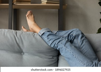 Crop close up of woman lying relaxing on comfortable grey couch in living room on lazy domestic weekend. Female renter or tenant rest barefoot on cozy sofa at home. Relaxation, pedicure concept.