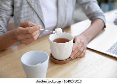Crop close up of woman sit at desk put cube of white sugar drinking warm hot tea at workplace. Female employee sweeten beverage, enjoy leisure break time at work. Hygge, dieting concept.
