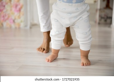 Crop close up of young biracial mom hold little infant toddler learn walking at home, small baby do make first steps with african American mother support and care, upbringing, maternity concept