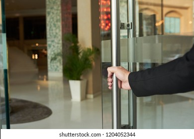 Crop doorman in black suit opening glass doorway of hotel welcoming guests