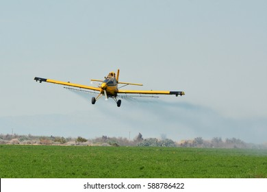 Crop duster airplane flying over alfalfa field in Imperial Valley, California.