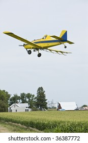 Crop duster over field of corn