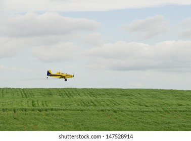 A crop duster spraying a filed