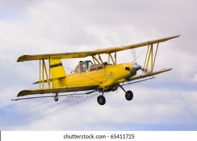 crop duster spraying insecticide on crops in central California