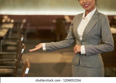 Crop elegant woman in suit making welcoming gesture inviting to visit restaurant in hotel