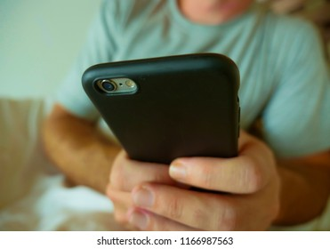 crop face portrait with close up hands holding mobile phone of young man at home bedroom using internet social media app on smartphone networking and texting lying on bed in lifestyle concept