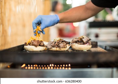 Crop faceless shot of person in gloves pouring cheese on burgers.