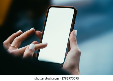 Crop faceless young stylish female browsing mobile phone with white empty screen tapping with finger on display standing on blurred street background