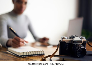 Crop female freelancer taking notes in notebook and preparing for photoshoot while sitting in office with computer and professional photo camera
