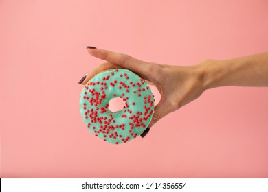 Crop female hand holding sweet blue donut isolated on pink background