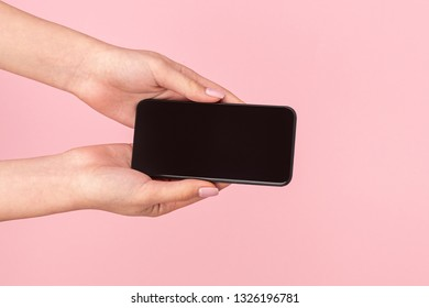 Crop female hands giving new innovative mobile phone on pink background