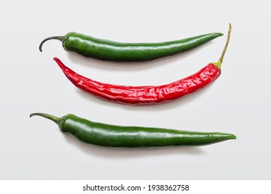 Crop of green and red hot chili peppers on a white background. Seasoning for lovers of spicy food