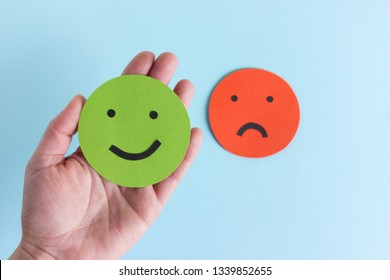 Crop hand holding green smiley giving positive rating on blue background