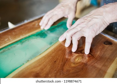Crop hands of carpenter working on beautiful table top with blue epoxy resin element