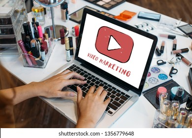 Crop hands of woman using laptop with makeup kits at table - video marketing and modern digital content marketing strategy concept