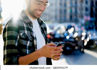 Crop happy young stylish male in casual outfit and eyeglasses enjoying coffee to go and messaging on smartphone in city street on sunny weather