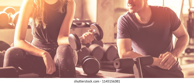 Crop image of beautiful sport girl with dumbbell in hand with personal trainer in professional gym, color filter effect selective focus.