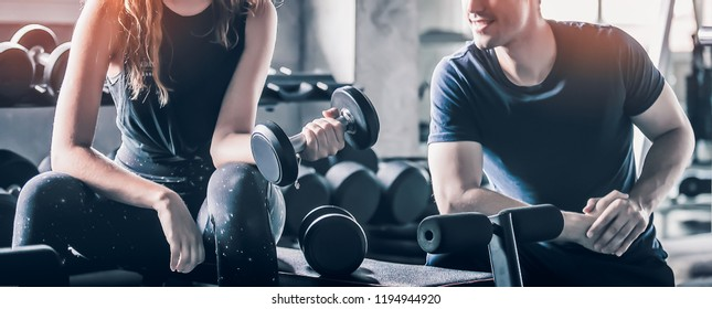 Crop image of beautiful sport girl with dumbbell in hand in professional gym color filter effect selective focus.