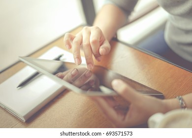 Crop image or closeup of a businesswoman is checking her email via tablet at the office. Her notebook and pencil are on the table. Smooth picture at working scenario.