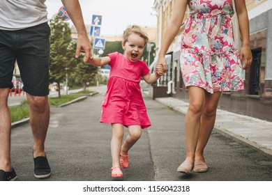 Crop image of family with little girl walking in city street