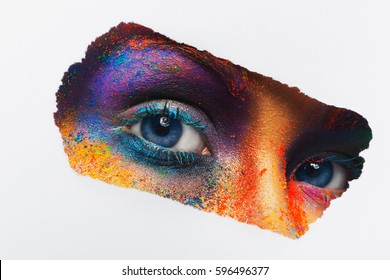 Crop image of female eyes with colorful powder make up looking to camera on white background. Beautiful fashion model with creative art makeup. Abstract colourful splash make-up. Holi festival