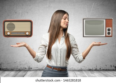 Crop image of young beautiful businesswoman, hands at sides, palms facing up, levitating retro radio set and outdated TV set. Retro vibes. Vintage collections. Analog technology.