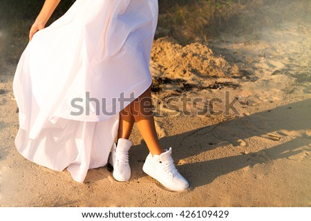 ad63fd9be ... Stock Photo (Edit Now) 426109429 - Shutterstock. Crop image of young  teen women wear white sneakers and long white dress and walking on