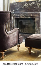 Crop of interior of fireplace in living room. Back view of cozy brown armchair and little chair near granite fireplace with elements of glass. Reflection on glass of fireplace.