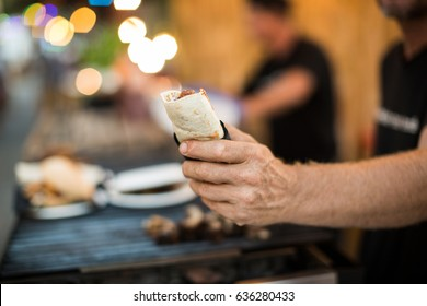 Crop male hand of vendor holding made burrito on blurred background of food truck.
