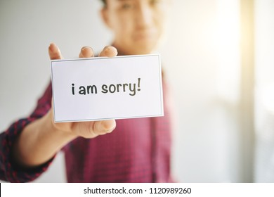 Crop male wearing checkered shirt?with I Am Sorry sign in hands