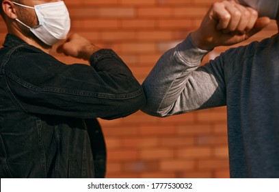 Crop men in masks greeting each other with elbow bump while keeping social distance during coronavirus epidemic on street