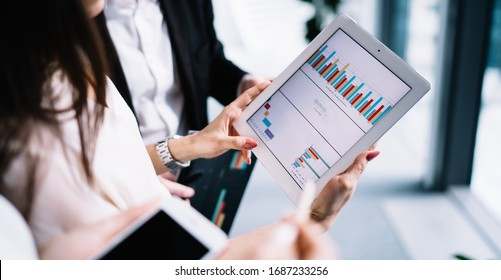 Crop modern office workers analyzing and discussing colorful statistical charts while sharing tablet coworking in modern office building in daylight