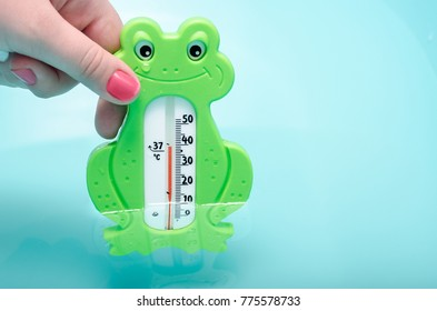 Crop mother using frog thermometer to measure temperature of water in baby's tub.