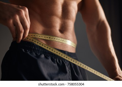 Crop muscular sportsman posing shirtless and measuring waist line with measuring tape.