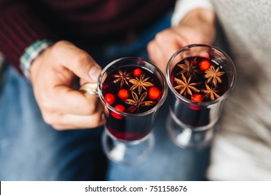 Crop people clinking with glasses full of mulled wine withs spices.