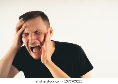 Crop person slapping scared man in face. Emotional male getting slapped in face while shouting with closed eyes in fear on white background