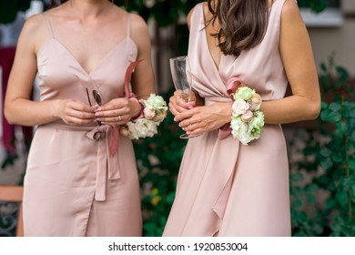 crop photo beautiful slender bridesmaids waiting for the ceremony to start. wedding look, identical dresses and butannieres from natural flowers