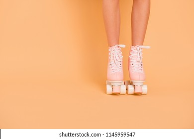 Crop photo of legs in vintage quad roller skates shoes isolated on pastel peach background with copy space for text