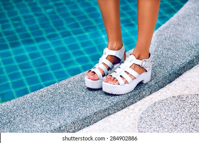 Crop photos. Female feet in white sandals with heels. It stands on the edge of the pool with blue water. Stylish image of trendy silver summer sandals.