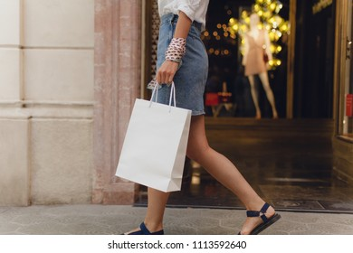Crop picture of girl walking with shopping bag on city streets while doing shopping. Stylish girl walking along clothes shop window. Concept of consumerism. Mockup of white paper shopping bag