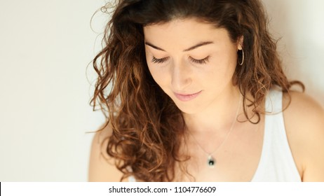 Crop portrait of attractive shy brunette with long curly hair looking down with slight smile.