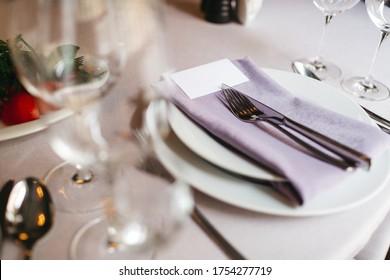 前景に皿、紫色のセルビエット、銀色のカトラリー、ぼかしたつる色の眼鏡をかけた食卓。 美しいレストランの優雅なケータリング、結婚式場の準備。 カフェのミニマリズムのコンセプト。