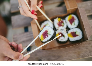 Crop shot from above of man and woman taking sushi with chopsticks from carton box