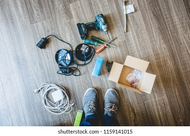Crop shot from above of person in sneakers standing on wood floor with set of instruments and cables for installing illumination