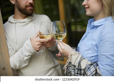 Crop shot of amorous Caucasian couple clinking glasses of white wine and looking at each other tenderly while celebrating anniversary