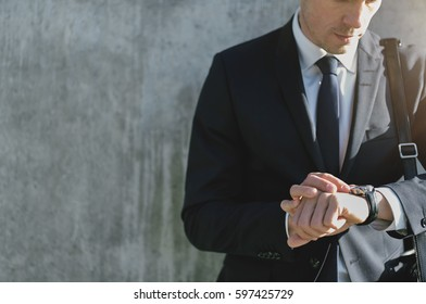 Crop shot of businessman wearing suit and checking time with wrist watch on background of grey wall