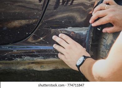 Crop shot of man inspects car scratch dent damage