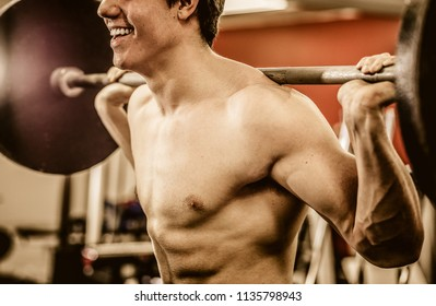 Crop shot of muscular shirtless man smiling while holding barbell on shoulders and working out.